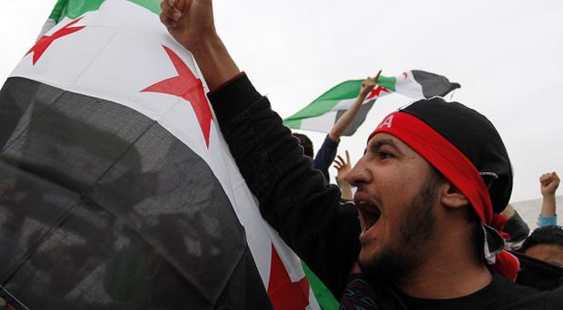 Syrian protesters chant anti-Bashar Assad slogans during a celebration to mark the second anniversary of the Syrian revolution, in Amman, Jordan (AP)