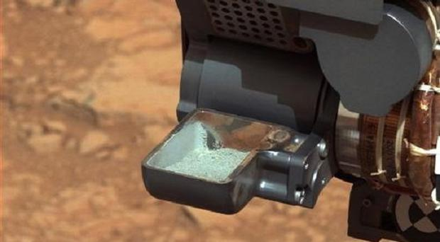 The Curiosity rover holds a scoop of powdered rock on Mars (AP/Nasa)