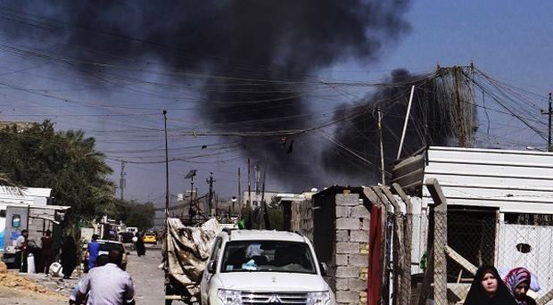 Smoke rises after a car bomb attack in Sadr City, Baghdad, amid a wave of coordinated bombings that killed dozens of people (AP)