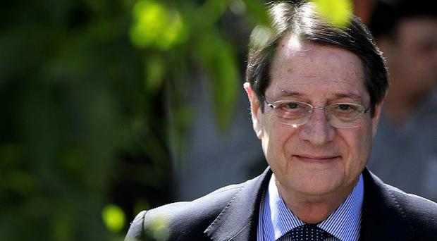 Cypriot president Nicos Anastasiades has been offered help by a senior cleric as the country battles a financial crisis (AP)