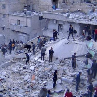 People search among the rubble of damaged buildings in the al-Zarazir neighbourhood of Aleppo, Syria (AP/AMC)