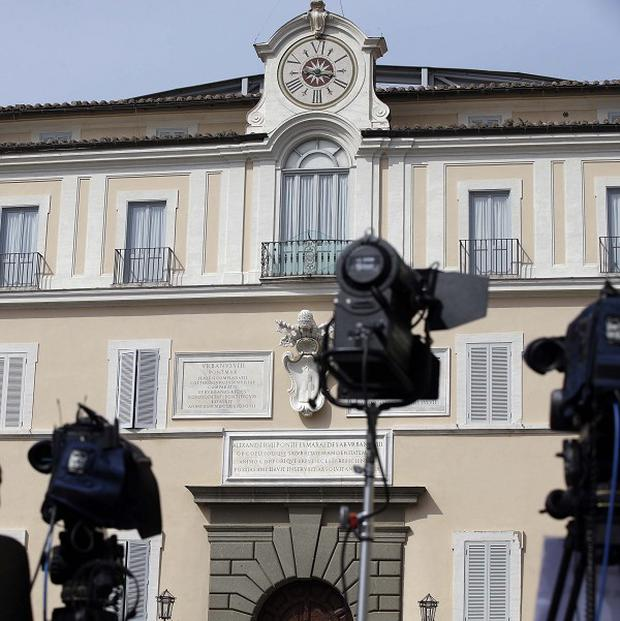 Journalists and TV crews stand in front of the papal residence in Castelgandolfo, in the outskirts of Rome (AP)
