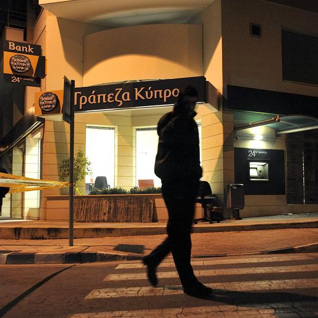 A security officer guards a branch of a Bank of Cyprus after a small bomb attack in Limassol (AP/Pavlos Vrionides)