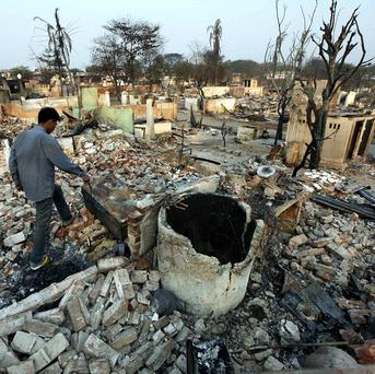 A man walks among the debris of buildings destroyed during ethnic unrest between Buddhists and Muslims in Meikhtila (AP)
