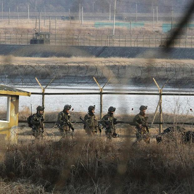 South Korean army soldiers patrol along a barbed-wire fence near the border village of Panmunjom in Paju, South Korea (AP)