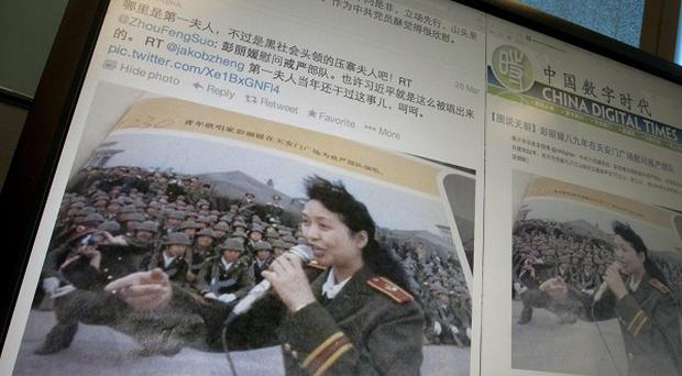 A computer screen shows sites displaying an undated photo of China's new first lady Peng Liyuan in younger days singing to martial law troops (AP)