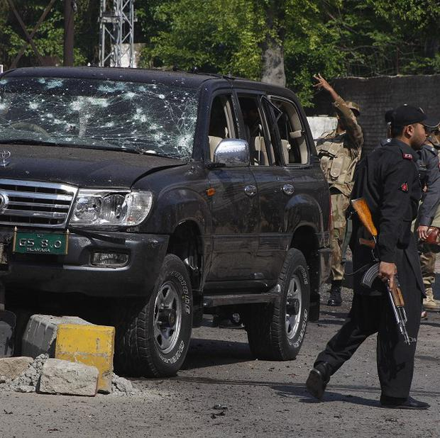 Pakistani troops gather next to a damaged vehicle at the site of a suicide bombing in Peshawar (AP)