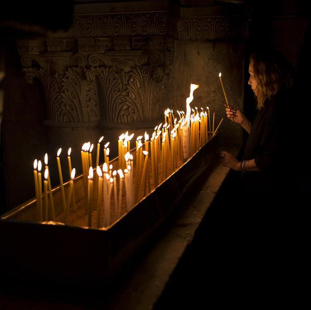 A Catholic pilgrim lights a candle inside the Church of the Holy Sepulchre, traditionally believed to be the site of the crucifixion of Christ (AP)