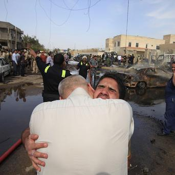 An Iraqi man is comforted at the scene of a car bomb attack in Baghdad (AP)
