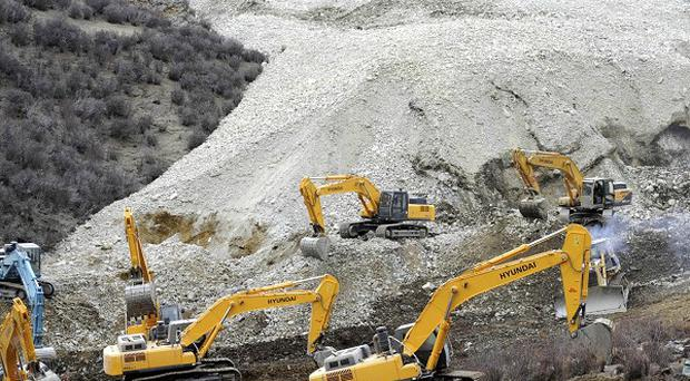 Earthmovers remove rocks and mud from the scene where a landslide hit a mining area in Maizhokunggar county of Lhasa in Tibet (AP)