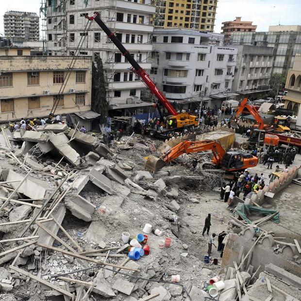 Rescuers using mechanical diggers remove rubble from the site of a collapsed building in downtown Dar es Salaam, Tanzania (AP)
