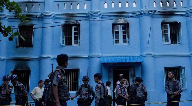 Police officers stand guard outside a mosque following a fire in Yangon (AP)