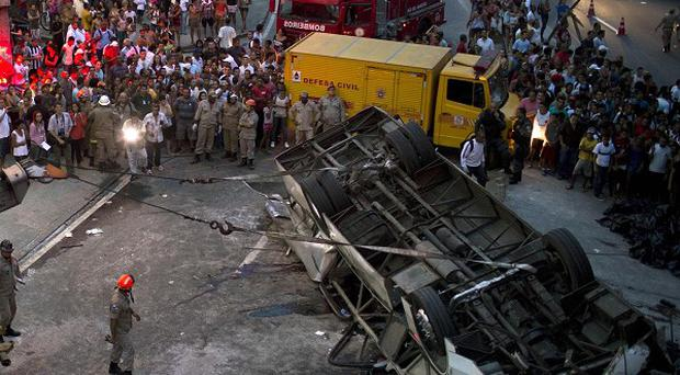 A bus is seen upside down after falling from a viaduct into Avenida Brasil, the largest avenue in Rio de Janeiro (AP)