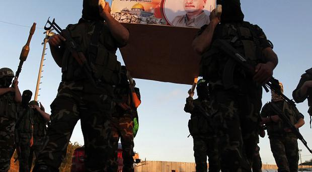 Militants carry a mock coffin of Maysara Abu Hamdiyeh, who died of cancer in an Israeli jail, in the Gaza Strip (AP)