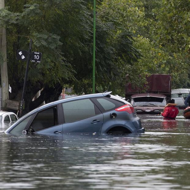 Rescue workers in a raft manoeuvre through a flooded street where cars are submerged along a street in La Plata (AP)