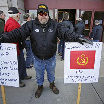 Gun rights protestor Paul Regish holds signs outside the legislative office building at the Capitol in Hartford, Connecticut (AP)