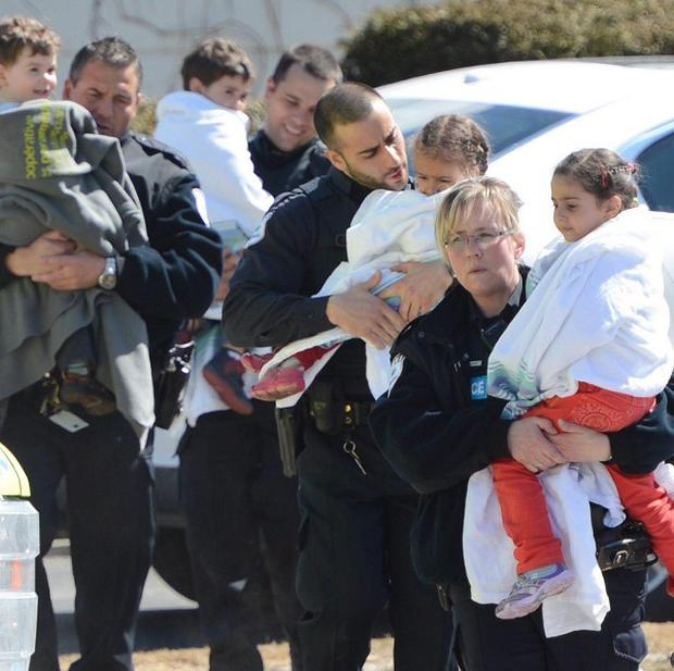 Police carry children from a safehouse to waiting parents and guardians after a shooting at a daycare centre in Quebec (AP)