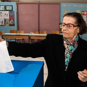 An elderly woman casts her ballot at a polling station in Podgorica, Montenegro (AP)