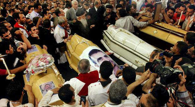 Egyptian Christians gather around four coffins during a funeral service, at the St Mark Coptic Cathedral in Cairo (AP)