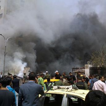 Smoke rises from burned cars after a huge explosion shook Sabaa Bahrat Square in Damascus, Syria (AP/SANA)