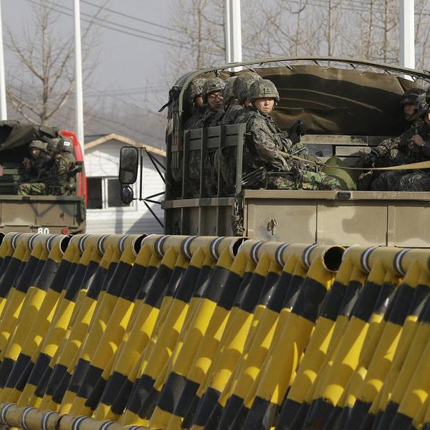 South Korean soldiers on their military trucks pass at barricaded Unification Bridge near the border village of Panmunjom (AP)