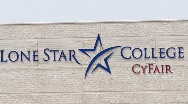 A police helicopter circles above the Lone Star Community College in Cypress, Texas (AP)