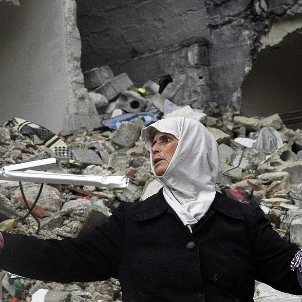 A Syrian woman stands amid the ruins of her house which was destroyed in an airstrike by government warplanes a few days earlier, killing 11 (AP)