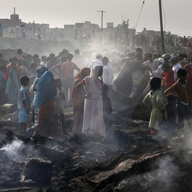 Residents salvage their belongings after a fire gutted their shanty town in New Delhi, India (AP)