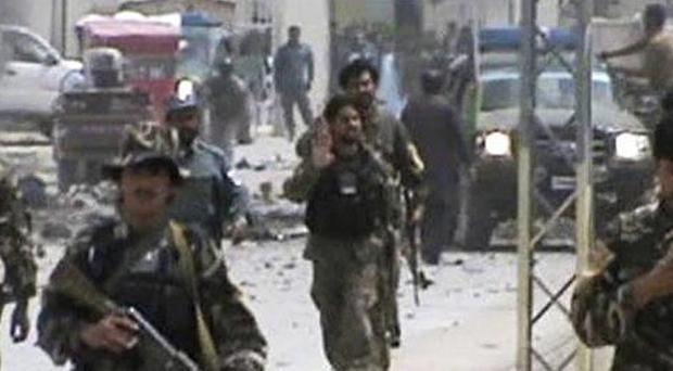 Afghan national army soldiers rush to the scene moments after a car bomb exploded in Qalat, Zabul province (AP)