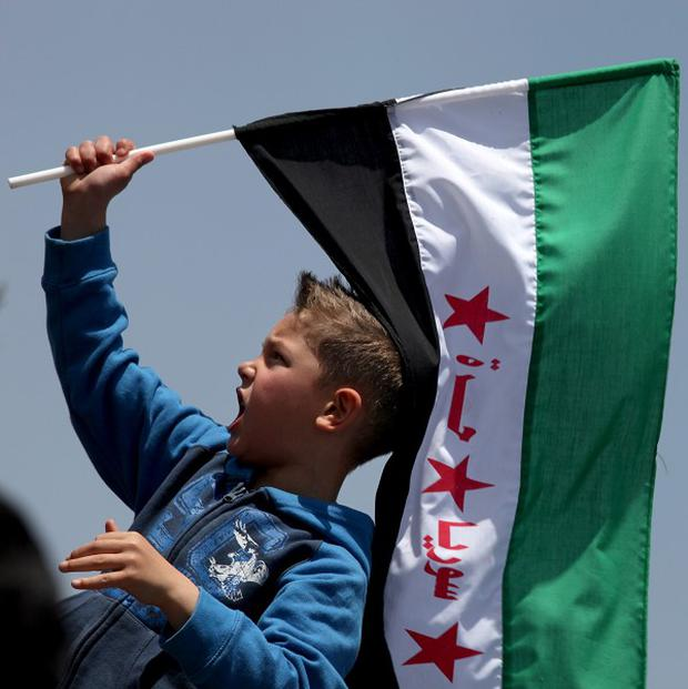 A boy waves the Syrian revolutionary flag as protesters chant anti-Bashar Assad slogans in Amman, Jordan (AP)