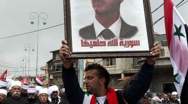 An Assad supporter holds up a picture of the president (AP)