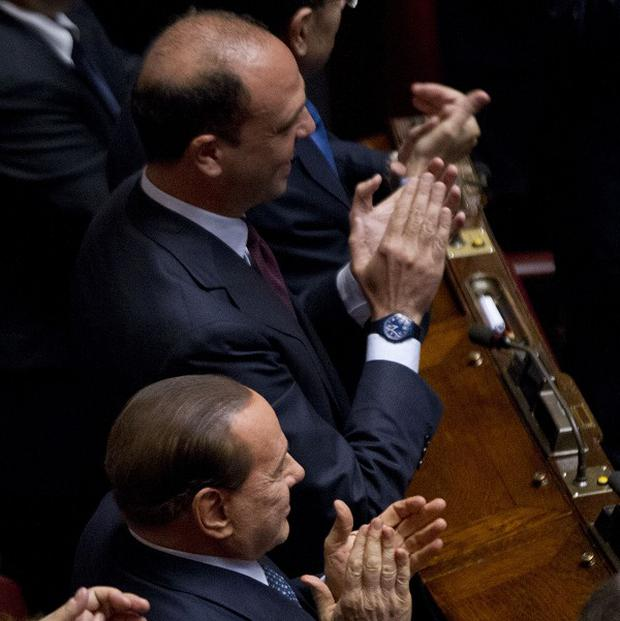 People for Freedom party president Silvio Berlusconi, bottom, and secretary Angelino Alfano applaud after Giorgio Napolitano was elected new Italian head of state (AP)