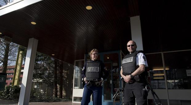 Two police officers in bullet proof vests are seen outside the closed Driestar College high school in Leiden (AP Photo)