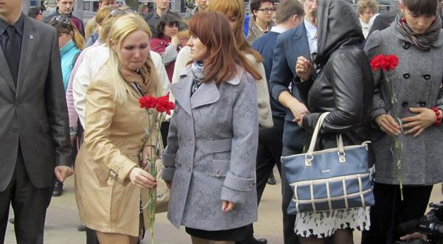 Residents lay flowers at the the site of a shooting in the south-west Russian town of Belgorod (AP)