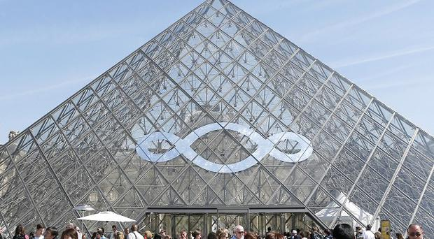 Italian artist Michelangelo Pistoletto's art work decorates the Louvre museum's iconic glass pyramid in Paris, France (AP)