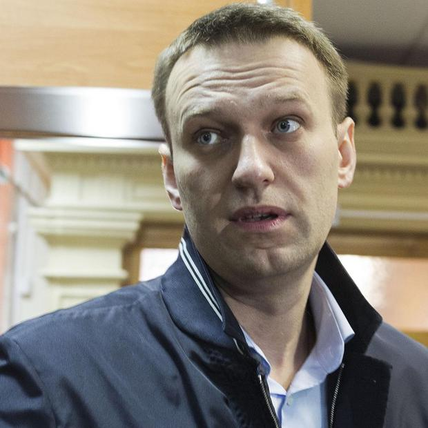 Opposition leader Alexei Navalny enters a courtroom to attend a trial in Kirov, Russia (AP)