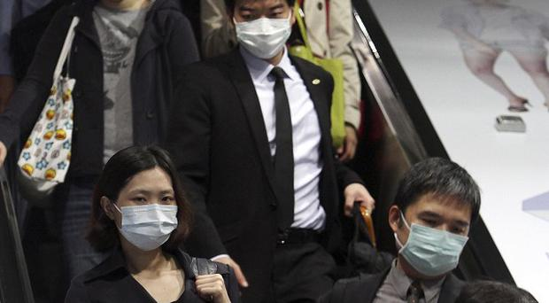 Commuters wear masks at a subway station in Taipei, Taiwan (AP/Chiang Ying-ying)