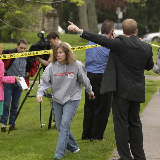 Parents and other family members cross under a police line to check on their children at LaSalle High School in Cincinnati (AP)