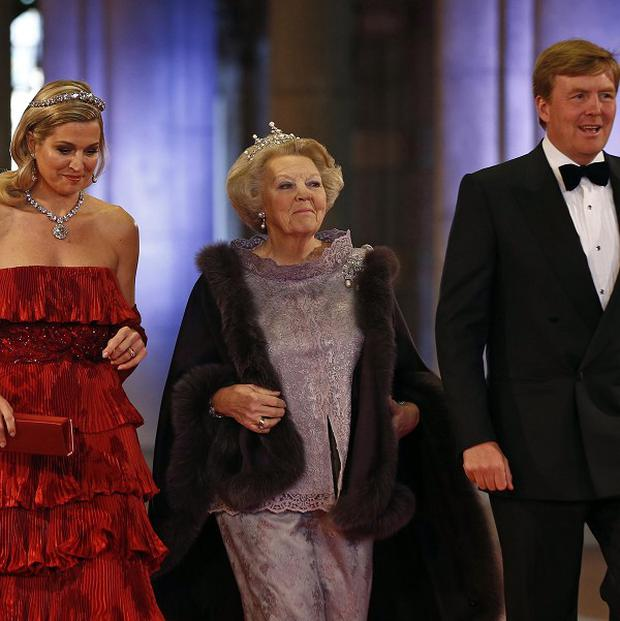Queen Beatrix, centre, and Crown Prince Willem-Alexander and his wife Princess Maxima arrive for a banquet at the Rijksmuseum (AP)