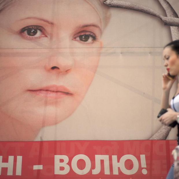 A woman passes a banner showing support for Yulia Tymoshenko near Independence Square in Kiev, Ukraine.