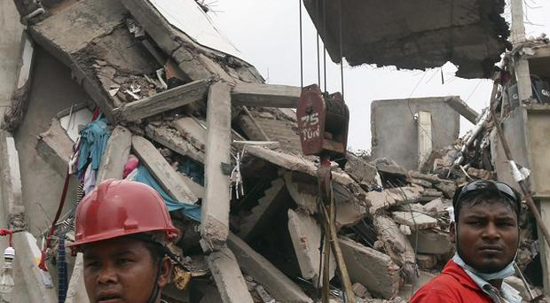 Workers watch as a crane lowers the ceiling of the garment factory building which collapsed in Savar, near Dhaka, Bangladesh (AP)