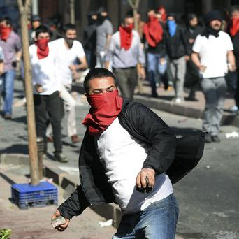 A protester prepares to throw a stone as clashes erupt between police and protesters during May Day celebrations in Istanbul (AP)