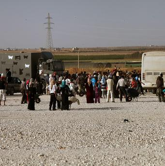 Syrian refugees carry their belongings in Jordan (AP)