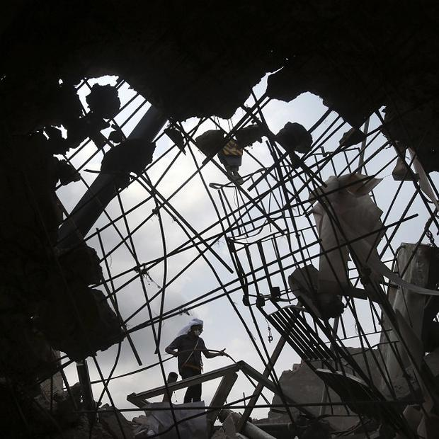 A worker is seen through a broken cement wall as he toils in the collapsed garment factory building in search for bodies (AP)