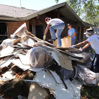 Students clean debris at a home in West, Texas, that was damaged due to the explosion at a fertiliser plant on April 17 (AP)