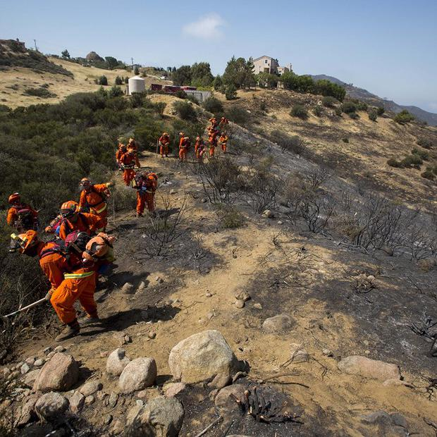 Crews work on the fire line after a wildfire near Point Mugu, California (AP)