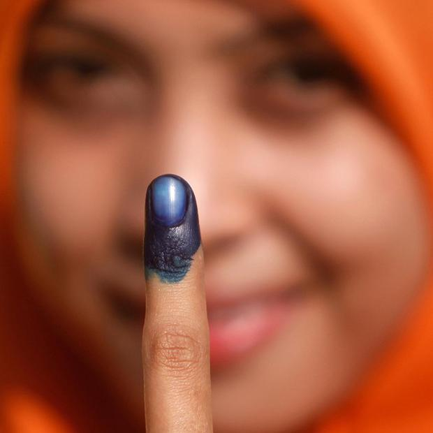A Malaysian voter shows her finger marked with indelible ink after casting her ballot in the general elections at a polling station (AP)