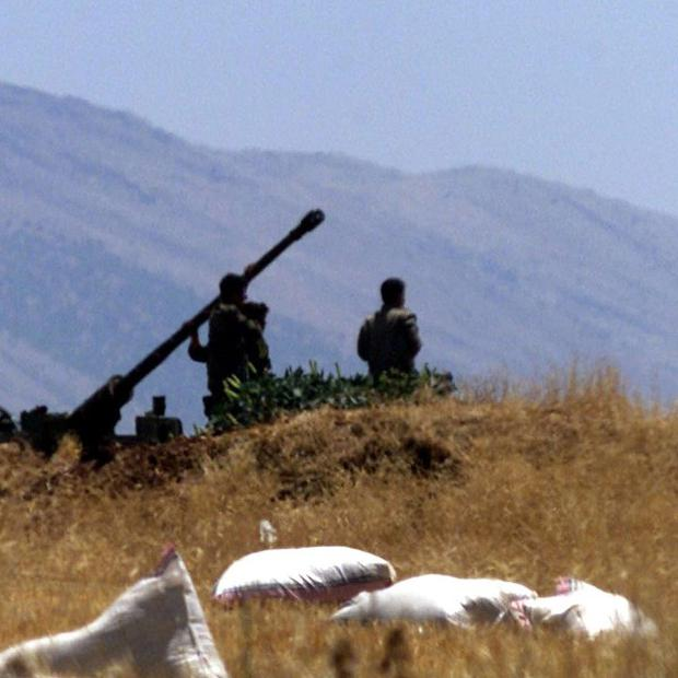 Syrian soldiers prepare an anti-aircraft gun near field of wheat close to a radar position in eastern Lebanon's Bekaa valley (AP)