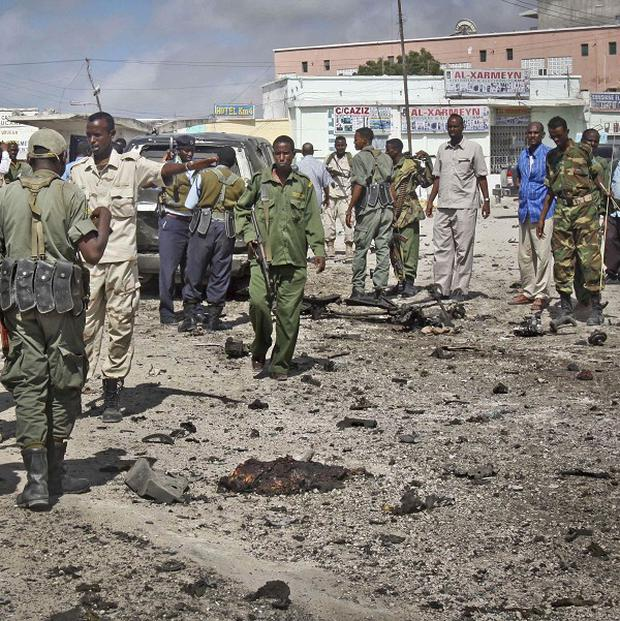 Somali soldiers gather at the scene of a suicide car bomb blast in the capital Mogadishu (AP)