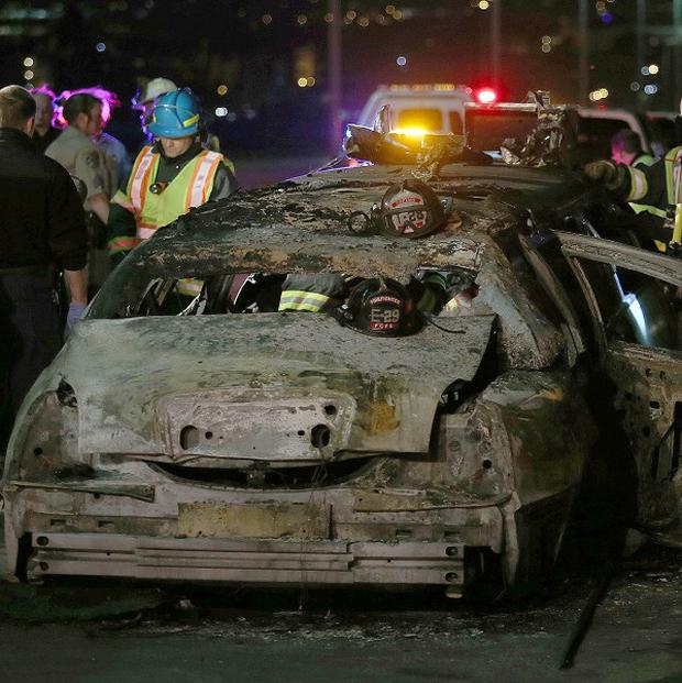 Firefighters and highway patrol personnel investigate the scene of a limousine fire (AP/Oakland Tribune-Bay Area News Group, Jane Tyska)